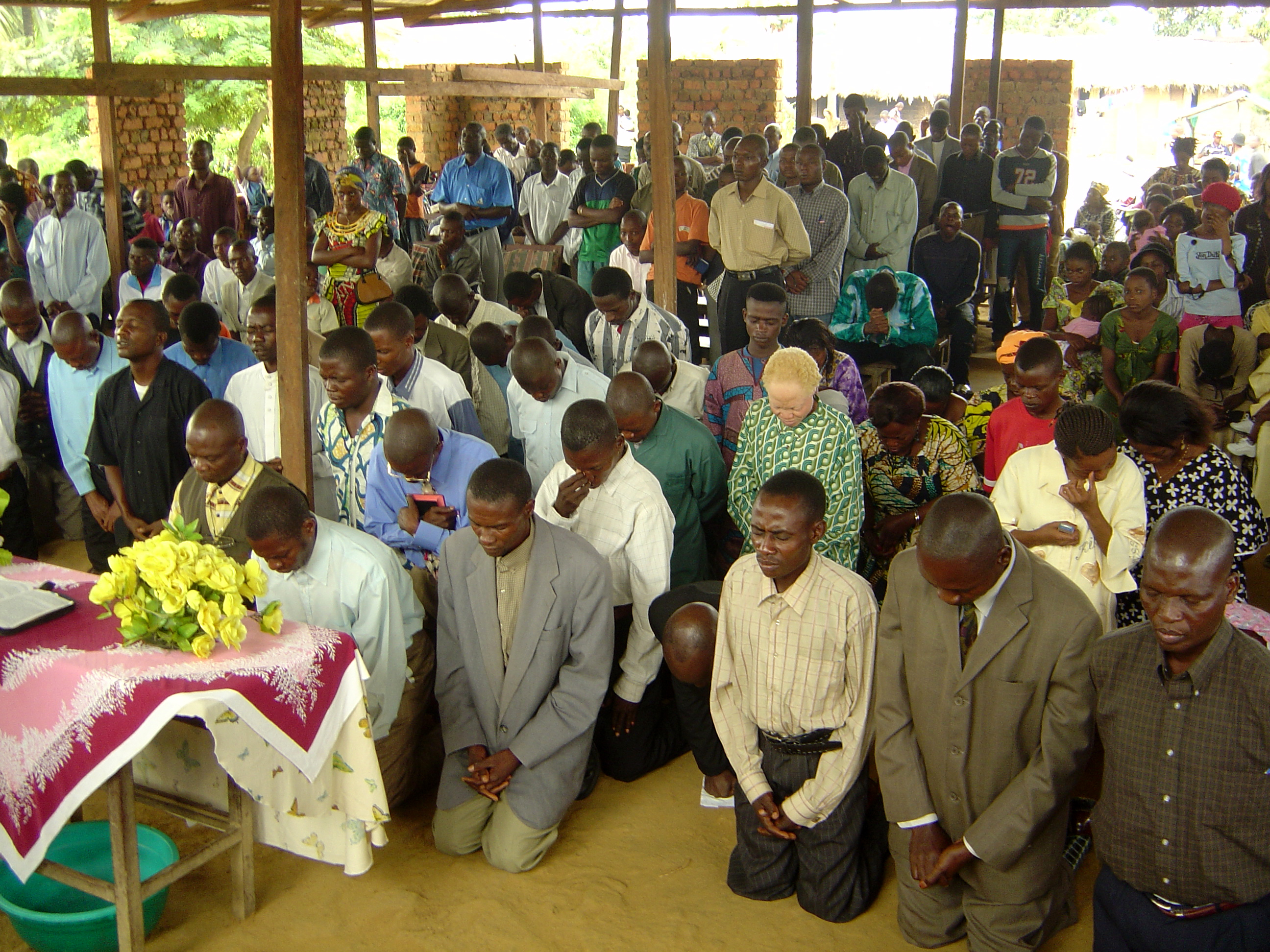 Church service in Kindu with new students praying at the altar
