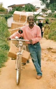 Student pushing bicycle loaded with Bibles